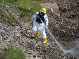 ERRS Tech power washing contaminated sediment from rocks inside retention pond.