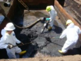 ERRS crew removing contaminated oil sludge from pit near incinerator.