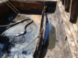 View of weit device in sludge pit near incinerator after partial removal of sludge.