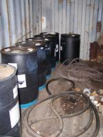 Drums of corrosive chemicals stored in CONEX with wooden flooring.