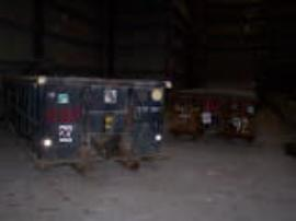 Roll-offs containing an unknown soil-like material staged inside empty warehouse.