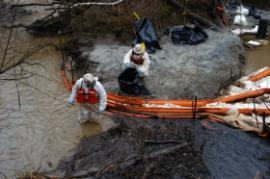 Operations removing oil and oil-contaminated debris at underflow dam following heavy rains.