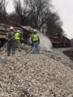 Dumping stone from rail car over embankment.