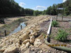 Flushing soils adjacent to track ballast to flush out crude oil for recovery in trench and on site treatment.
