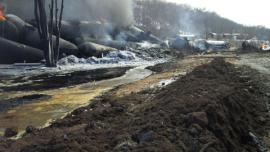 Derailed rail cars on fire. Soil berm with spilled oil to contain spilled oil is in the foreground. <br />Date Taken: 3/6/2015<br />Category: Site Photo<br />Latitude: <br />Longitude: <br />Tags:
